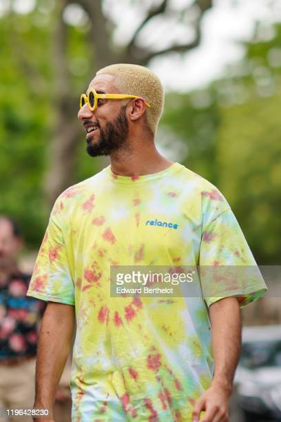 A guest wears yellow Chanel sunglasses a watercolor yellow red and light blue tshirt outside Heron Preston during Paris Fashion Week Menswear...