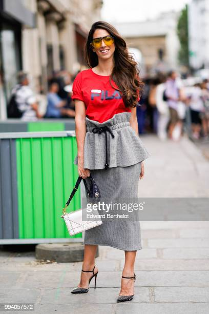 A guest wears yellow glasses a red FILA tshirt with a printed logo a gray skirt gray heels shoes a silver shiny Diorama Dior bag outside JeanPaul...