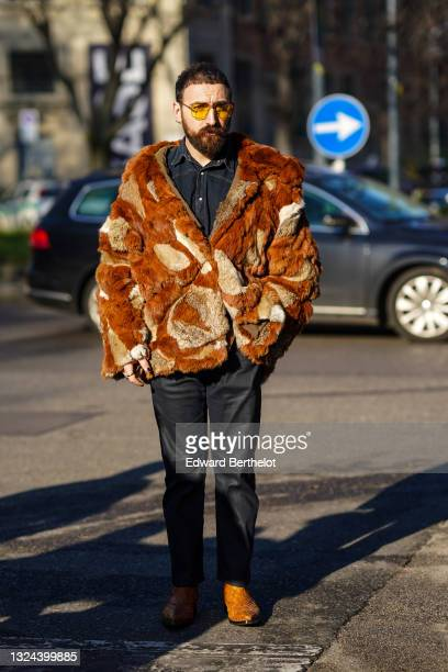 Guest wears yellow sunglasses, a blue denim jean shirt, a camel and brown pattern fur oversized coat, black denim jean pants, camel shiny leather...
