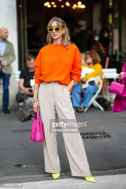 Guest wears yellow sunglasses, a neon orange wool pullover, beige high waist suit pants, gold and brown earrings, pearls bracelets, a neon shiny...