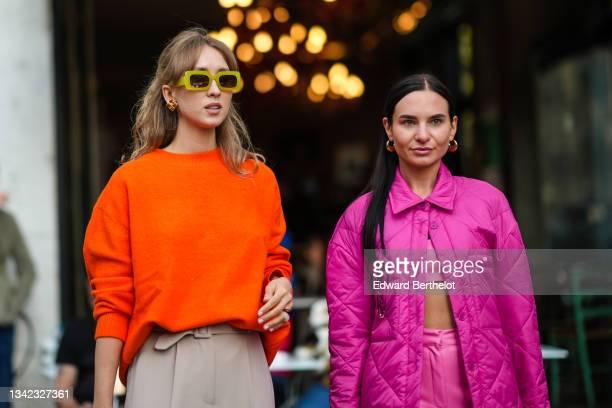 Guest wears yellow sunglasses, a neon orange wool pullover, beige high waist suit pants, gold and brown earrings, pearls bracelets, a guest wears...