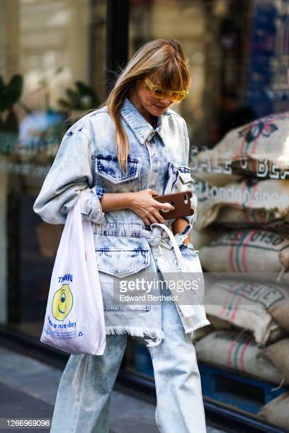Guest wears yellow sunglasses, a pale blue denim jacket, during London Fashion Week September 2019 on September 14, 2019 in London, England.