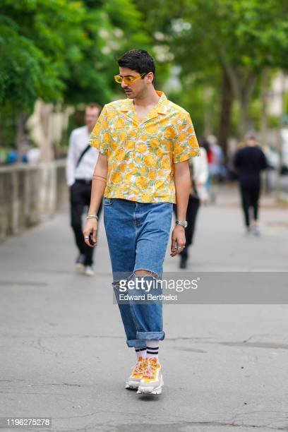 Guest wears yellow sunglasses,bracelets, rings, a short sleeves shirt with oranges pattern, blue ripped crop jeans with rolled-up hem, yellow and...