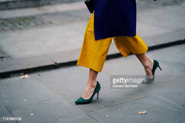 Guest wears yellow wide-leg crop pants, green suede high-heeled pumps, during London Fashion Week February 2019 on February 18, 2019 in London,...