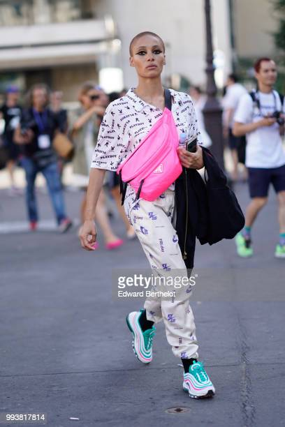 A guest wearsa pink shoulder strap bag a Playboy white shirt white pants sneakers shoes with green shoelace outside Fendi during Paris Fashion Week...