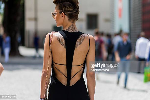 A guest with a backless dress and tattoo and updo hair during Pitti Uomo 90 on June 15 in Florence Italy