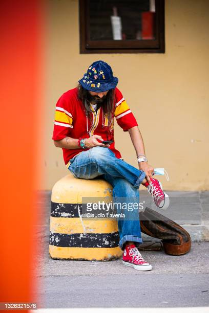 Guest with blue jeans hat, red shirt, jean, Louis Vuitton backpack, red sneakers seen at Fortezza Da Basso on June 30, 2021 in Florence, Italy.
