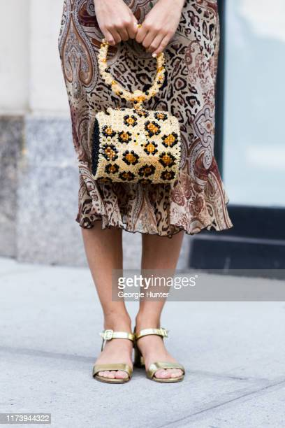 Guest with Susan Alexandra leopard print plastic handbag with round handle is seen during New York Fashion Week on September 11 2019 in New York City