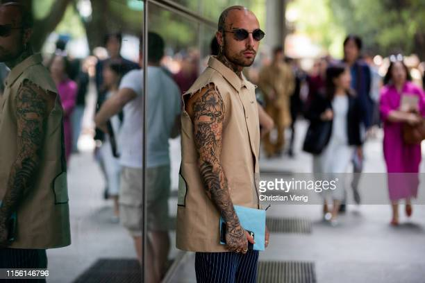 A guest with tattoos is seen wearing beige sleeveless jacket outside Emporio Armani during the Milan Men's Fashion Week Spring/Summer 2020 on June 15...