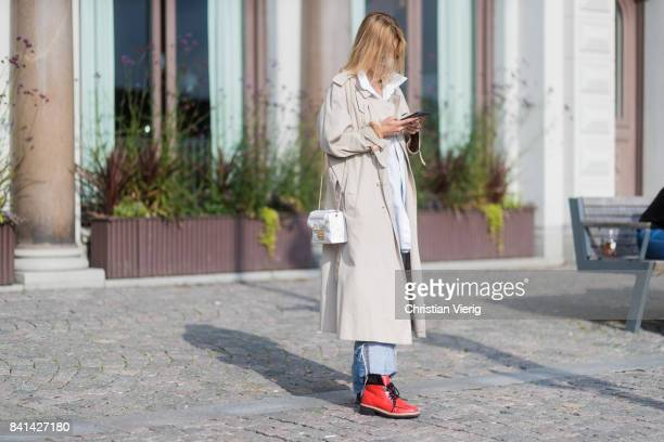 A guest writting a text message wearing creme trench coat outside House of Dagmar on August 31 2017 in Stockholm Sweden