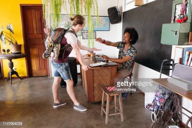 guesthouse owner handing room keys to backpacker - hostel stock pictures, royalty-free photos & images