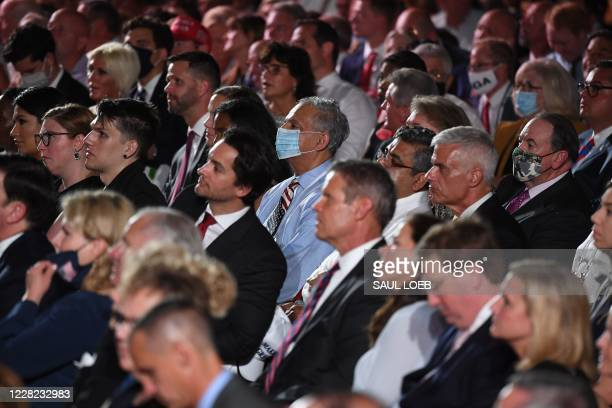 Guests, a few wearing masks, watch US President Donald Trump delivers his acceptance speech for the Republican Party nomination for reelection during...