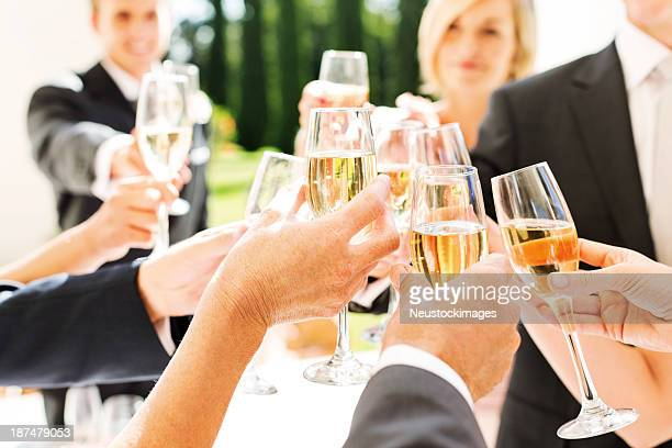 Guests And Couple Toasting Champagne Flutes At Wedding Reception