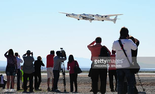 Guests and media watch as WhiteKnightTwo takes flight carrying SpaceShipTwo over Spaceport America, northeast of Truth Or Consequences, on October...