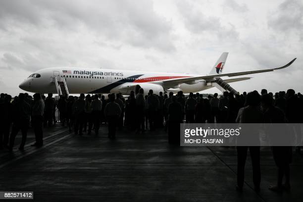 Guests and members of the media watch and take pictures of a Malaysia Airlines Airbus A350 aircraft from a hangar at an engineering complex adjacent...