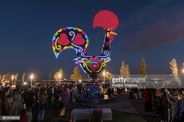 Guests and public observe as Led lights are switched on during the inauguration of Pop Galo Portuguese artist Joana Vasconcelos public art work...