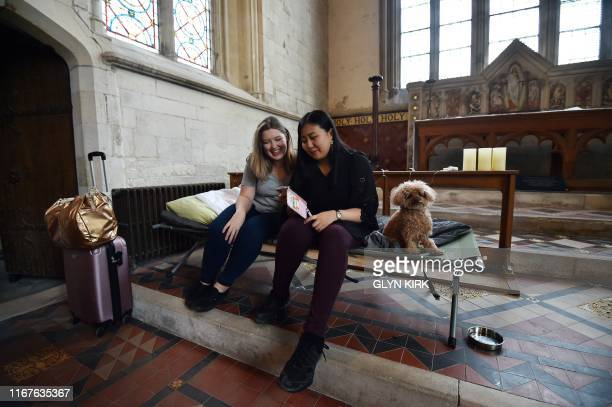Guests Andrea Stewart and Kae Ono sit with Coco the dog as they settle in at St Mary's Church, where guests can pay to stay overnight in what is...
