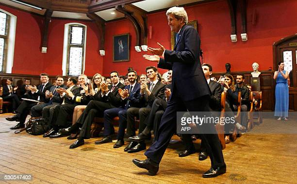 TOPSHOT Guests applaud US Secretary of State John Kerry as he arrives to speak at the Oxford Union in Oxford central England on May 11 2016 John...