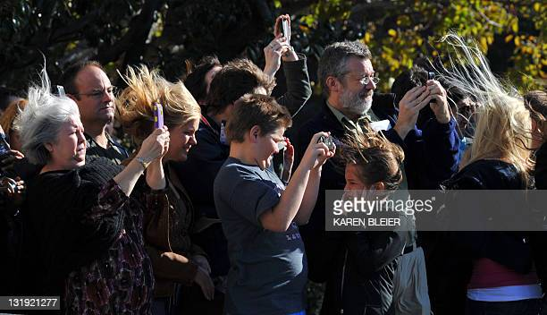Guests are blown by wind from the rotors of Marine One as it lifts off from the South Lawn with US President Barack Obama on board at the White House...