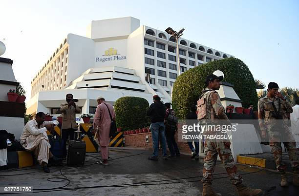Guests are gather outside a Regent Plaza Hotel following a fire in the Pakistan's port city of Karachi on December 5 2016 A predawn fire at a hotel...