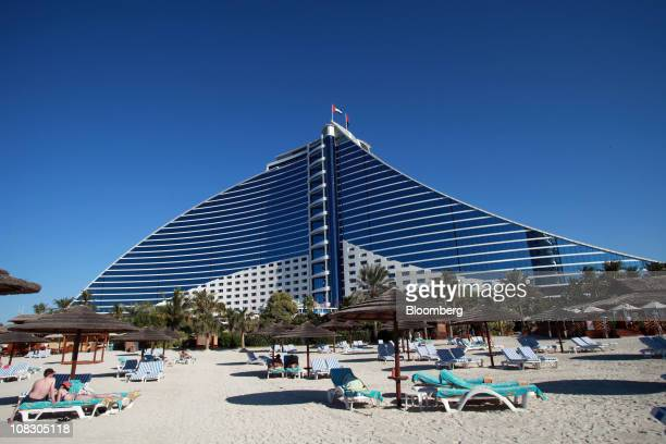 Guests are seen on sun loungers outside the Jumeirah Beach hotel operated by the Jumeirah Group LLC in Dubai United Arab Emirates on Monday Jan 24...
