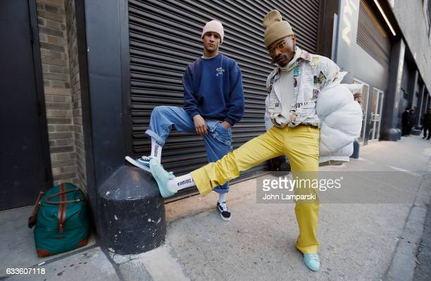Guests are seen wearing a white down jacket yellow slacks newsprint design shirt jeans seatshirt and watch caps outside the General Idea fashion show...