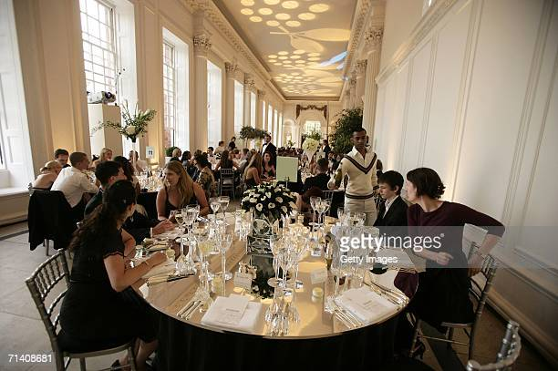 Guests are served by waiters in traditional tennis dress at the 'Summer Tennis Soiree with the Stars' dinner hosted by EBS and the Laureus Sport for...