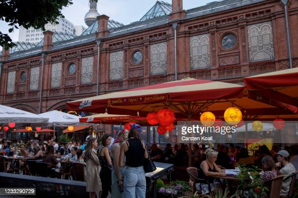 Guests are sitting in a restaurant at Hackescher Market on the second day that people are no longer required to show a negative Covid test result to...