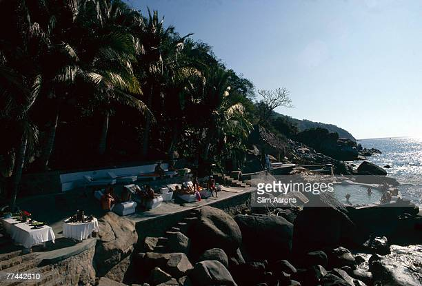 Guests around the seaside pool at Warren Avis's villa in Acapulco Mexico January 1978