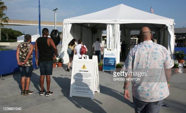 Guests arriving at the Magic Kingdom theme park wait to get their temperatures checked before entering the theme park at Walt Disney World on the...