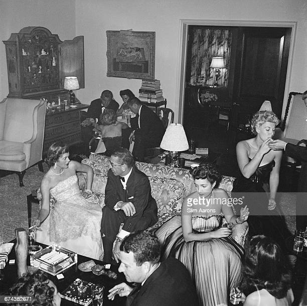 Guests at a party given by Mrs Gary Cooper in Beverly Hills, California, 1952. She is on the left, seated on the couch with Mr Van Herbick and Jack...