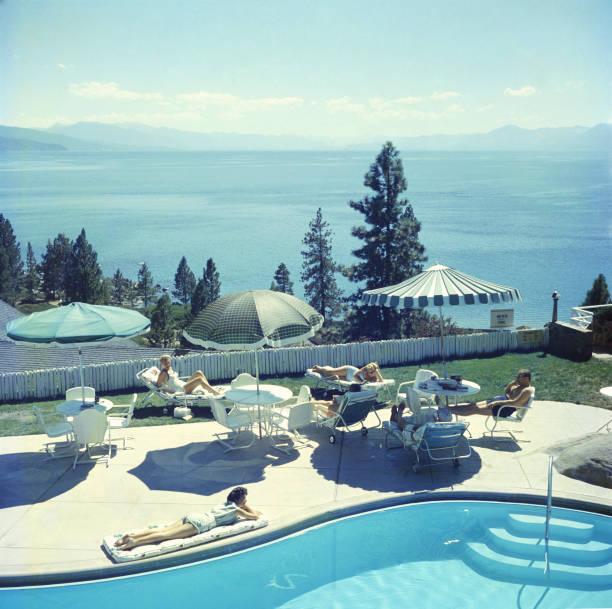 A group of people relaxing by a pool near Lake Tahoe,...
