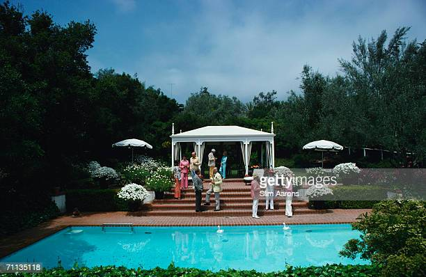Guests attend a poolside luncheon at the home of Dorothy Laughlin in Santa Barbara California May 1975