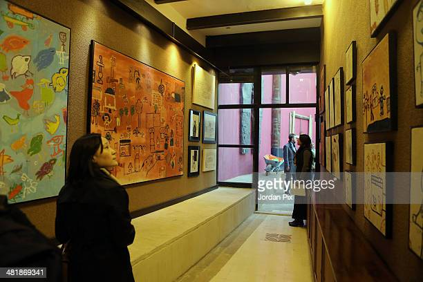 Guests attend the opening of the exhibition 'Colours of Resilience Work from a children's street art project from north Jordan and Syrian refugee...