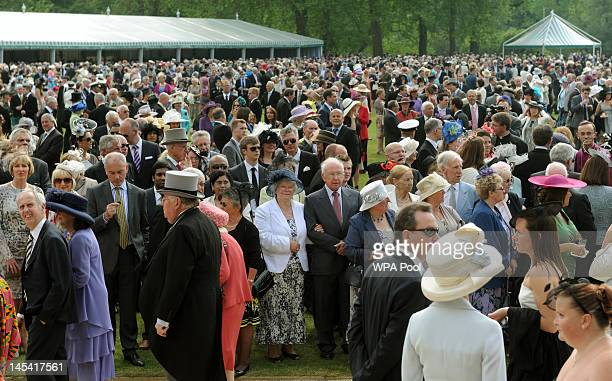 Guests await the arrival of Queen Elizabeth II during a garden party at Buckingham Palace on May 29 2012 in London England