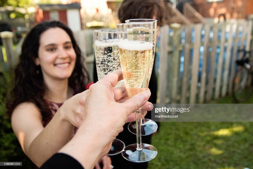 Guests cheering at a wedding cocktail backyard party during Covid-19. : Stock Photo