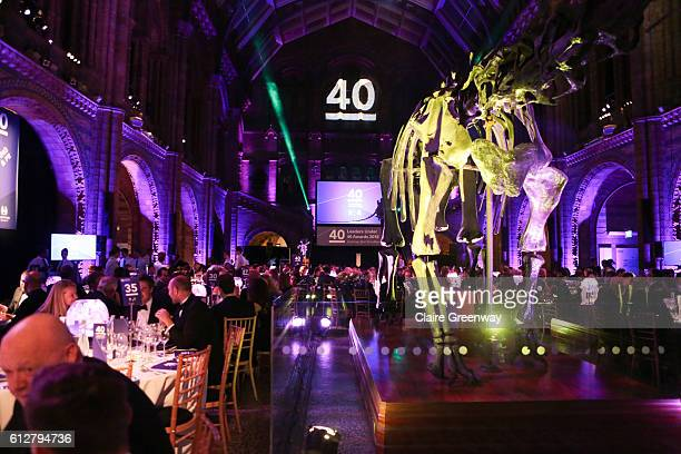 Guests dine around the Diplodocus skeleton cast in the Hintze Hall during the Leaders Under 40 Awards at the Natural History Museum on October 4 2016...