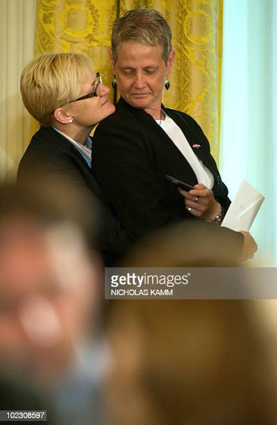 Guests embrace while waiting for US President Barack Obama to address a Lesbian Gay Bisexual and Transgender Pride Month event in the East Room of...