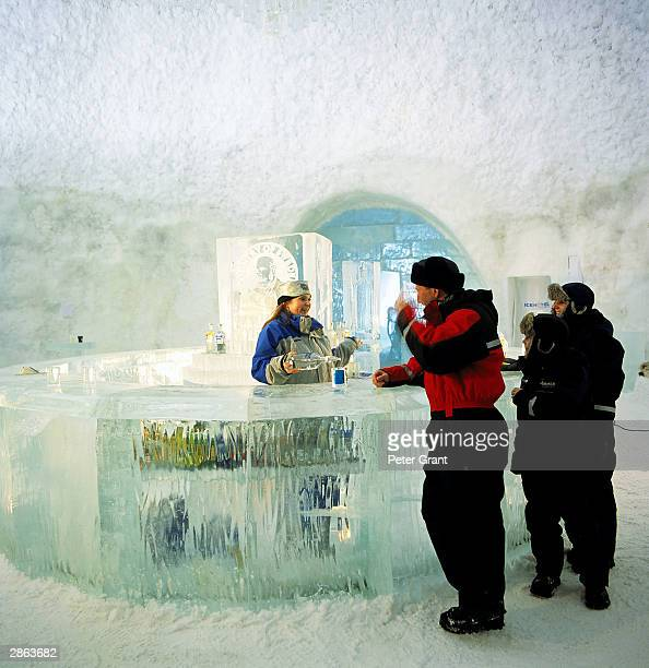 Guests enjoy a drink in the Absolut Ice Bar at the Ice Hotel January 2002 in Jukkasjarvi Sweden The 30 000 square foot hotel is constructed anew...