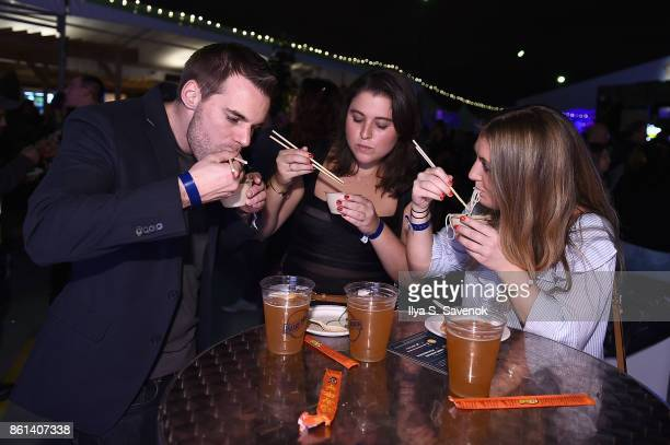 Guests enjoy noodles at the Food Network Cooking Channel New York City Wine Food Festival presented by CocaCola Rooftop Iron Chef Showdown Battle...