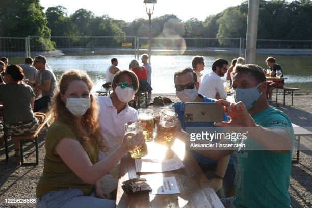 Guests enjoy the atmosphere of the Seehaus beer garden in the English Garden park on the first day beer gardens were allowed to reopen in Bavaria...