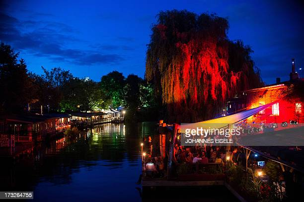 Guests enjoy the summer night in a bar called 'Club der Visionaere' in Berlin Germany on July 10 2013 AFP PHOTO / JOHANNES EISELE