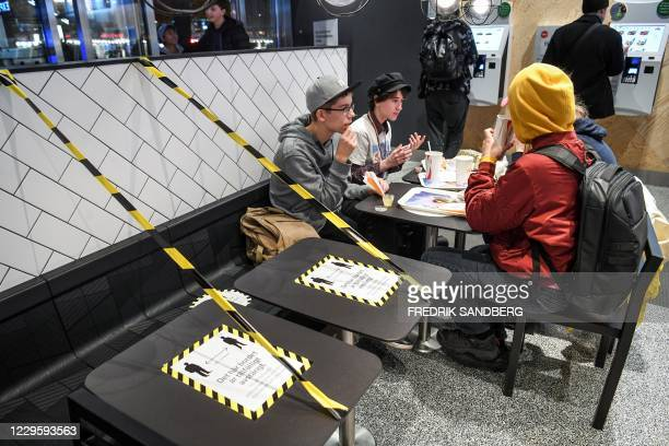 Guests enjoy their meal at a fast food restaurant next to taped off tables in central Stockholm on November 12 amid the ongoing novel coronavirus...