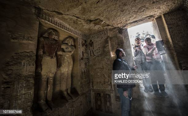 Guests enter a newlydiscovered tomb at the Saqqara necropolis 30 kilometres south of the Egyptian capital Cairo on December 15 belonging to the high...