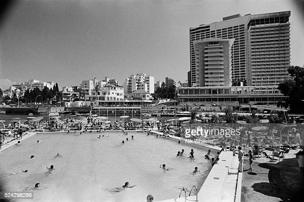 Guests fill the swimming pool and garden of the St Georges Beach Club The Phoenicia Intercontinental Hotel rises in the background