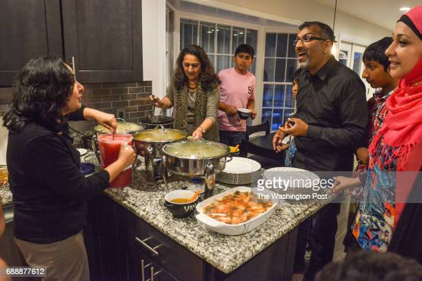 Guests gather around chafing dishes in the kitchen Tariq Rehman and his wife Sonia host a small Iftar to break fast for Ramadan in their home on July...