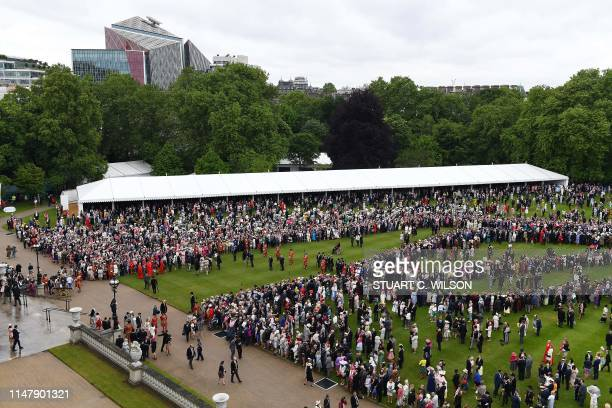 Guests gather on the lawn during the Queen's Garden Party at Buckingham Palace central London on May 29 2019