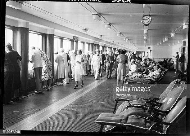 Guests gaze out windows aboard the Normandie the epitome of luxury liners at the time