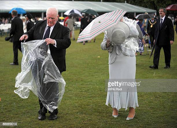 Guests head cover up as heavy rain begins to fall during the first Royal Garden Party of the summer at Buckingham Palace on July 7 2009 in London...