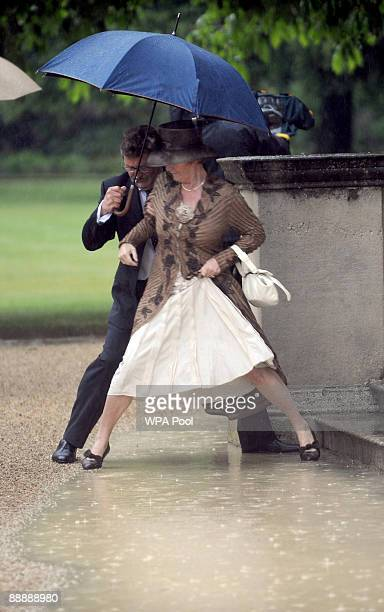 Guests head for cover as heavy rain falls during the first Royal Garden Party of the summer at Buckingham Palace on July 7 2009 in London England